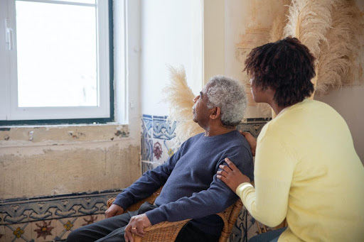 An elderly person and his caregiver
